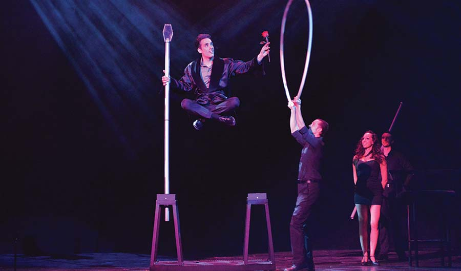Magician Michael Grandinetti levitating on stage.