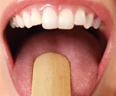 Dentist performs an oral examination.