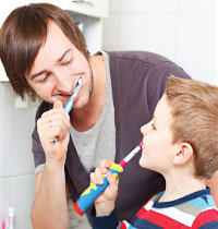 Father brushing teeth with child.