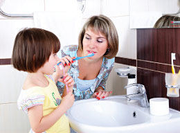 Mother teaching child how to brush her teeth.