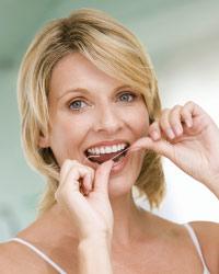 Pregnant woman flossing teeth.