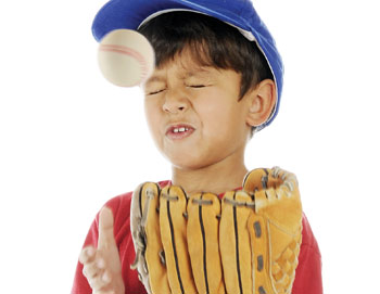 Image of a child wearing a baseball glove with a ball falling toward his face