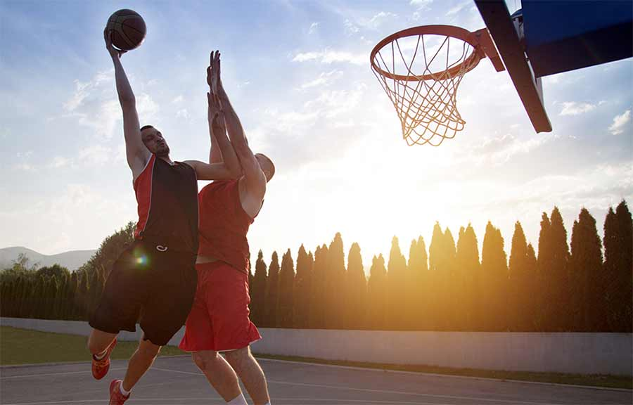 Two men playing one-on-one basketball on an outdoor court.